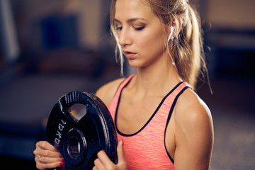 Woman working out with weight plates. Healthy lifestyle concept.