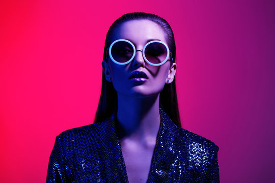 Fashion girl with long hair and round sunglasses in a black shining dress poses in neon light in the studio