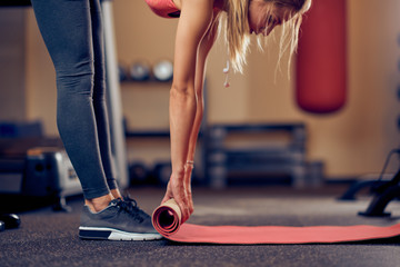 Caucasian woman unwinding the mat and preparing for exercises. Gym interior. healthy lifestyle concept.