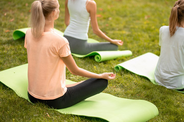Young slim girl sits relaxing in the lotus position doing exercises on yoga mats with other girls on green grass in the park on a warm day. Wall mural