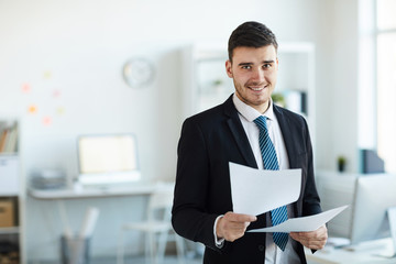 Smiling young successful banker in elegant suit looking through financial documents in office