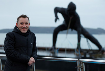 "The sculptor Joseph Hillier poses for a photograph near his latest artwork, ""Messenger"", Britain's largest bronze sculpture, as it arrives by barge in Plymouth Sound before being transported to the Theatre Royal in Plymouth"