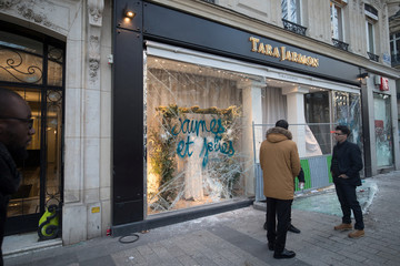 """People stand in front of a damaged Tara Jarmon shop during a demonstration by the """"yellow vests"""" movement on the Champs Elysees avenue in Paris"""
