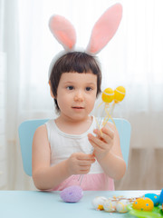 Little girl in bunny ears are playing with Easter eggs. Kids celebrating Easter.