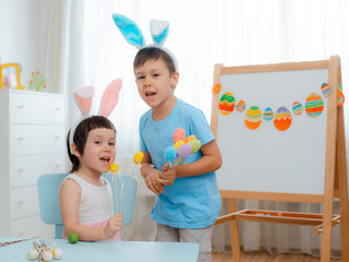 Little boy and girl in bunny ears are playing with Easter eggs. Kids celebrating Easter.