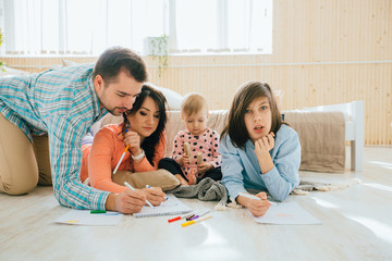Young happy family of four drawing together while lying on floor at home. New home, happy healthy relationship concept.