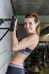 Young happy woman working her arms muscles in the Gym