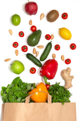 Photo of paper bag with vegetables and fruits. Flat lay composition with fresh vegetables on white background. Healthy food background. Shopping vegetarian food supermarket concept. Top view.