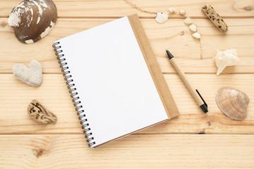 Flat lay con un cuaderno, un bolígrafo y bonitas conchas marinas. Concepto: planeando un viaje veraniego.