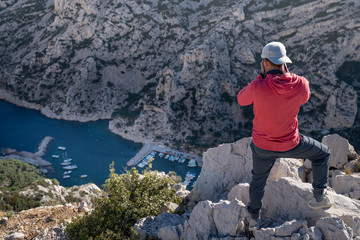 Hiker on top of cliff takes picture of the mediterranean sea - Marseille - Calanques of Sugiton (France)
