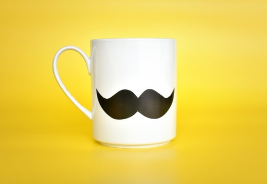 White mug with mustache on yellow background, Happy fathers day, International men day, Boss day concept.