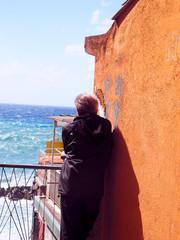 man looking at sea by old waterfront building Riomaggiore Cinque Terre Italy