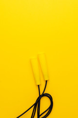 skipping rope with yellow handles on the yellow background