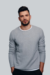 Irresistible man. Charming young man looking at camera and keeping hands in pockets while standing against grey background