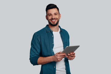 Ready to help. Handsome young man holing digital tablet and looking at camera with smile while standing against grey background