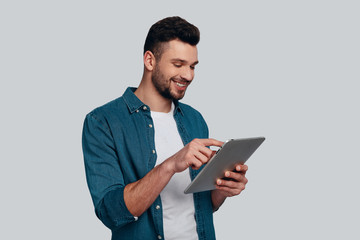 Technologies in everyday life. Charming young man using his digital tablet and smiling while standing against grey background