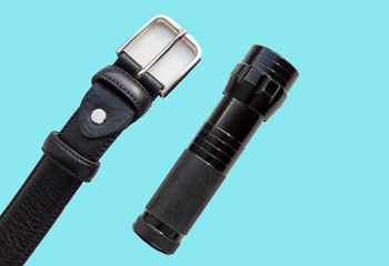 Men's accessories black leather strap and flashlight isolated on blue background