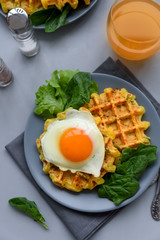 Spinach cheese waffles with fried egg on gray wooden background. Selective focus. Top view.