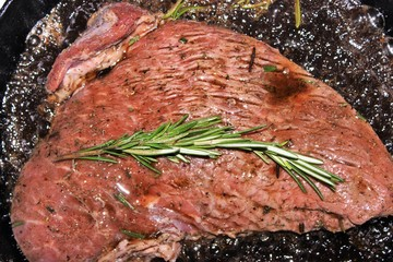 A large juicy steak of marbled beef is fried in a cast iron pan.