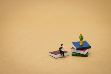 little kids Miniature people standing on books using as background Education concept and Learning...