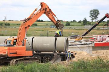 Fototapeta Rozładunek kręgów betonowych na budowie.