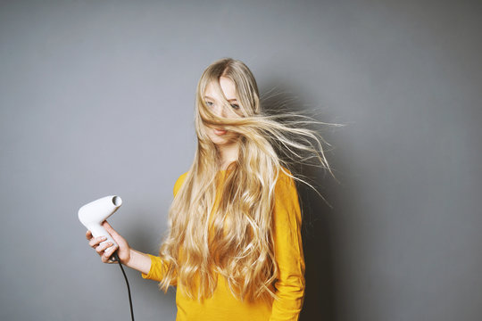funny young blond woman blow-drying her long hair with blow dryer