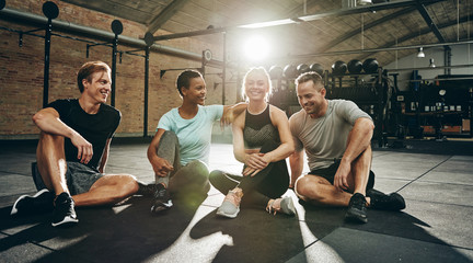 Laughing friends sitting and talking together after a gym workou