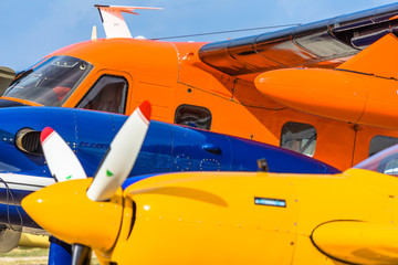Abstract picture of several historical small aircrafts, cut and depicted one behind the other, yellow, blue and orange airplane