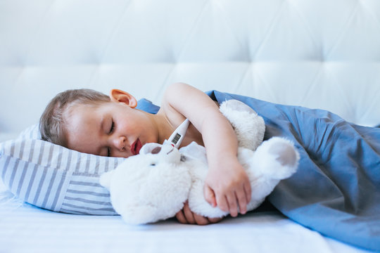the little boy is sick in bed with a thermometer and high temperature
