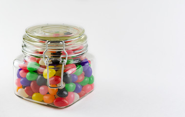 An assortment of jelly beans in a glass jar with clasp lid.  Isolated on white background.  Copy space on right side.