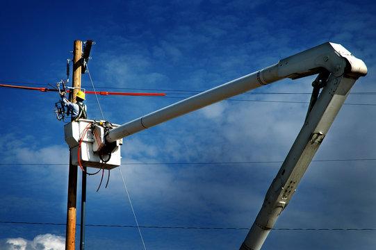 Man Worker Working on Power Lines Crane Bucket High in the Air Dangerous