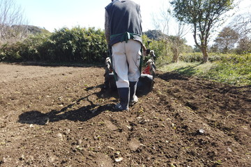 rear view : Senior farmer driving cultivator in the field - Agriculture / farmer's lifestyle