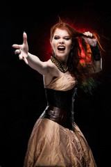 Beautiful redhead cosplayer girl wearing Victorian-style steampunk dress screams, pulls her hair by her hand and outstretching her hand. Red and black background