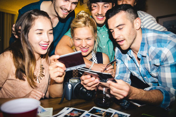 Happy multiethnic friends watching photographs at table in home during party