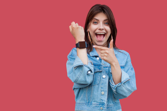 Portrait of surprised happy beautiful brunette young woman in denim casual style standing showing and pointing at screen of her smart watch with shocked face. studio shot, isolated on red background.