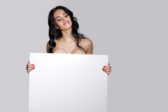 seductive naked brunette woman holding empty board. attractive sexy girl with blank board with copy space