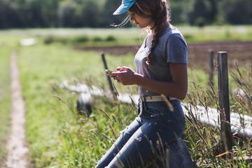 Teenage girl using smartphone at farm on sunny day