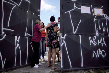 A student is received during a reopening day of the school, after the shooting in the Raul Brasil school in Suzano
