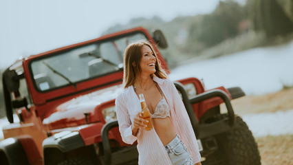 Young woman standing by a red car and drinks refreshment