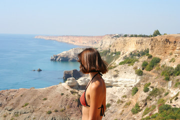 Beautiful picture of blue sea with mountains near and young woman standing