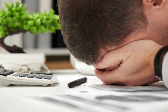 Tired businessman sleeping in an office. Business financial accounting concept.