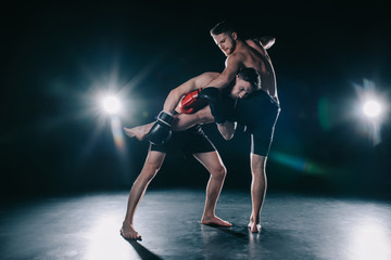 barefoot strong muscular mma fighter in boxing gloves clinching another while sportsman kicking him