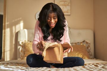 happy african american woman unboxing package in bedroom