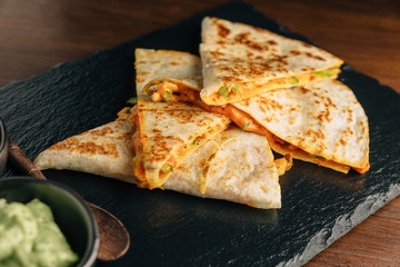 Close up Baked Chicken and Cheese Quesadillas served with Salsa and Guacamole on stone plate.