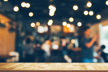 wooden table in front of abstract blurred coffee shop lights background