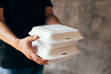 Close-up of delivery man handing a slack of foam lunch box - Foam box is toxic plastic waste. Used for recycling and environment saving concept