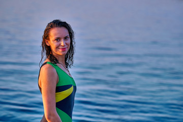 Portrait of a black-haired wet middle-aged woman in a swimsuit on a summer evening in the light of the setting sun.