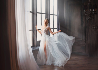 gorgeous image of graduate in 2019, girl in long white light gentle flying dress with bare leg stands alone, swan princess before performing on ballet stage, elegant lady with blond hair in sunlight