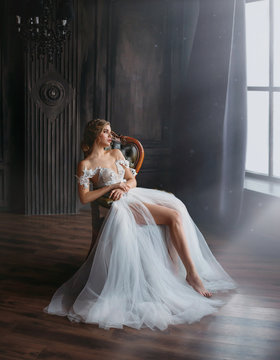 majestic and proud princess girl in white chic oriental white silver dress tired sitting on chair, lady shows off her slender leg and waiting for prince, gentle stylish image of graduate 2019