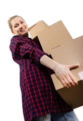moving to new house - smiling young woman with stack of cardboard boxes